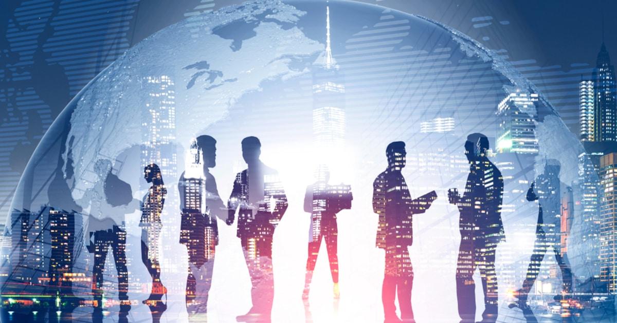 businessmen huddled together in front of world globe